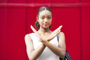 赤い壁の前で「NG」のハンドサインをする若いビジネスウーマンの写真素材 [FYI04911651]