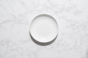 大理石の板に置かれた白いお皿の写真素材 [FYI04911677]