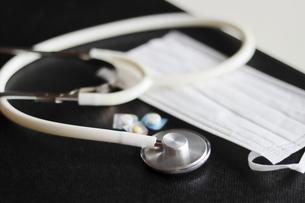 診察を行う医師のデスク上にある聴診器とマスクの写真素材 [FYI04911918]