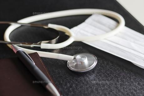 診察を行う医師のデスク上にある聴診器とマスクの写真素材 [FYI04911944]