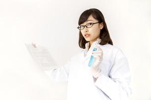 文献と試験管を持つ白衣を着た理系女子の立ち姿の写真素材 [FYI04912048]