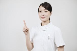指さしのポーズをする白衣の女性 の写真素材 [FYI04912472]