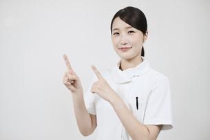 指さしのポーズをする白衣の女性 の写真素材 [FYI04912473]