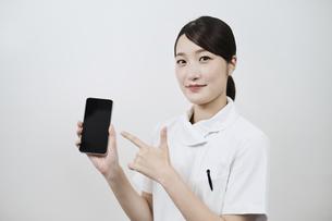 スマートフォンを操作する白衣の女性 の写真素材 [FYI04912887]