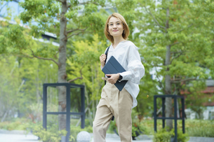 緑あふれるオフィス街を歩く女性の写真素材 [FYI04913513]