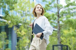 緑あふれるオフィス街を歩く女性の写真素材 [FYI04913515]