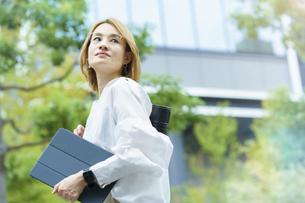 緑あふれるオフィス街を歩く女性の写真素材 [FYI04913516]