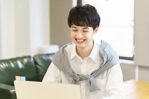 カジュアルな空間でノートパソコンを使う若い男性の写真素材 [FYI04914293]