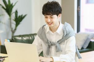 カジュアルな空間でノートパソコンを使う若い男性の写真素材 [FYI04914294]