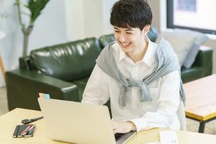 カジュアルな空間でノートパソコンを使う若い男性の写真素材 [FYI04914297]