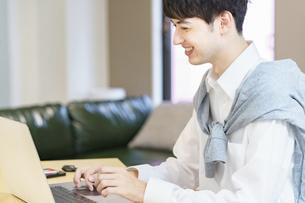 カジュアルな空間でノートパソコンを使う若い男性の写真素材 [FYI04914298]