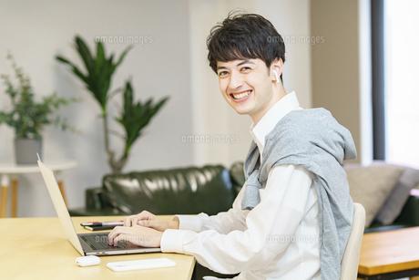 カジュアルな空間でノートパソコンを使う若い男性の写真素材 [FYI04914300]