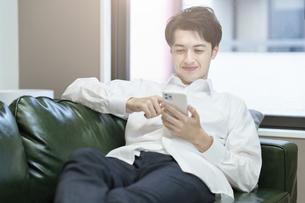 ソファでくつろぎながらスマートフォンを操作する男性の写真素材 [FYI04914308]