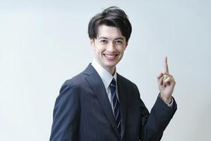 人差し指を立てるポーズをするビジネスマンの写真素材 [FYI04914335]