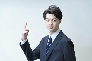 人差し指を立てるポーズをするビジネスマンの写真素材 [FYI04914336]