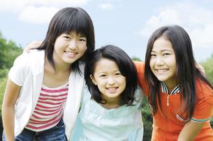 肩を組んで笑顔の女の子3人の写真素材 [FYI04914454]