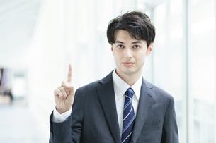 人差し指を立てるポーズをするビジネスマンの写真素材 [FYI04914479]