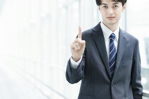 人差し指を立てるポーズをするビジネスマンの写真素材 [FYI04914491]