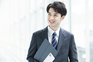 笑顔で通路を歩くビジネスマンの写真素材 [FYI04914503]