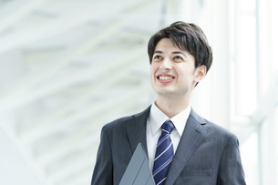 笑顔で通路を歩くビジネスマンの写真素材 [FYI04914506]