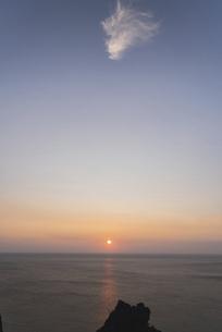 礼文島からの夕日~岩と雲の間に~の写真素材 [FYI04914890]