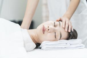 エステサロンで頭部をマッサージされる若い女性の写真素材 [FYI04915087]