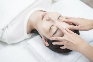 エステサロンで頭部をマッサージされる若い女性の写真素材 [FYI04915091]