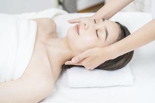 エステサロンで頭部をマッサージされる若い女性の写真素材 [FYI04915126]
