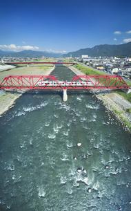 赤い鉄橋を渡るれいんどりーむ号の写真素材 [FYI04915412]