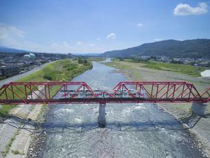 赤い鉄橋を渡るれいんどりーむ号の写真素材 [FYI04915421]