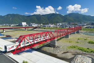 赤い鉄橋を渡るれいんどりーむ号と太郎山の写真素材 [FYI04915433]