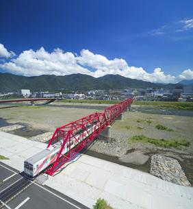 赤い鉄橋を渡るれいんどりーむ号と太郎山の写真素材 [FYI04915436]
