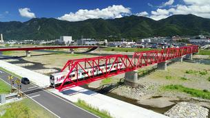 赤い鉄橋を渡るれいんどりーむ号と太郎山の写真素材 [FYI04915438]
