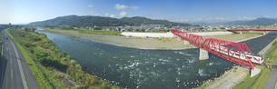 赤い鉄橋を渡るれいんどりーむ号と千曲川のパノラマの写真素材 [FYI04915440]