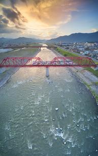 赤い鉄橋を渡るれいんどりーむ号と夕焼けの写真素材 [FYI04915467]