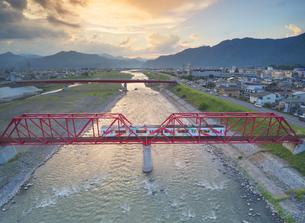 赤い鉄橋を渡るれいんどりーむ号と夕焼けの写真素材 [FYI04915468]