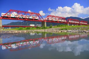 赤い鉄橋を渡る輝くれいんどりーむ号の多重露出と水鏡の千曲川の写真素材 [FYI04915472]