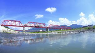 赤い鉄橋を渡る輝くれいんどりーむ号とハートの雲と千曲川の写真素材 [FYI04915477]