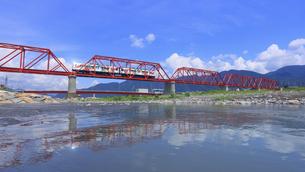 赤い鉄橋を渡る輝くれいんどりーむ号と千曲川の写真素材 [FYI04915481]