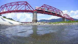 赤い鉄橋を渡るれいんどりーむ号と千曲川の写真素材 [FYI04915486]