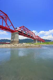 赤い鉄橋を渡るれいんどりーむ号と千曲川の写真素材 [FYI04915488]