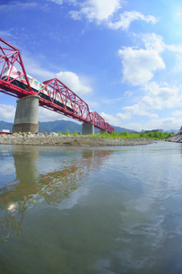 赤い鉄橋を渡る輝くれいんどりーむ号と千曲川の写真素材 [FYI04915493]