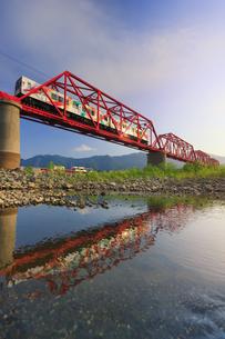朝の赤い鉄橋を渡るれいんどりーむ号と水鏡の千曲川と太郎山遠望の写真素材 [FYI04915500]