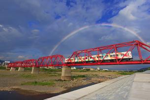 夕方の赤い鉄橋を渡るれいんどりーむ号とダブルレインボーの写真素材 [FYI04915507]