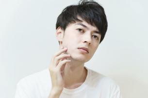 肌の状態を確かめる若い男性の写真素材 [FYI04915781]
