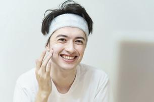 顔にクリームを塗る若い男性 の写真素材 [FYI04915801]