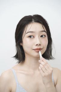 口紅を唇に塗る若い女性の写真素材 [FYI04915836]
