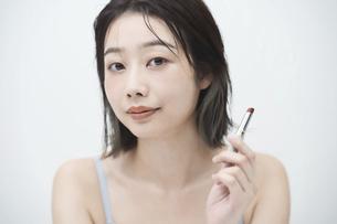口紅を唇に塗る若い女性の写真素材 [FYI04915843]