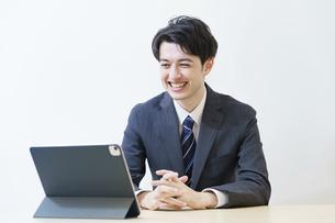 リラックスした表情でオンライン面接・会議・打ち合わせに臨むスーツ姿の男性 の写真素材 [FYI04915872]