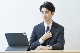 緊張した表情でオンライン面接・会議・打ち合わせに臨むスーツ姿の男性の写真素材 [FYI04915874]